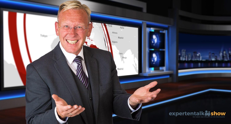 So kennt man ihn aus dem Fernsehen. TV und Talkshow Moderator Dirk Rabis vor TV-Studio-Kulisse der ExpertenTalkshow